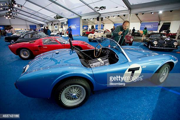 An attendee takes a photograph of a 1962 Shelby 260 Cobra automobile during the 2014 Pebble Beach Concours d'Elegance in Pebble Beach California US...