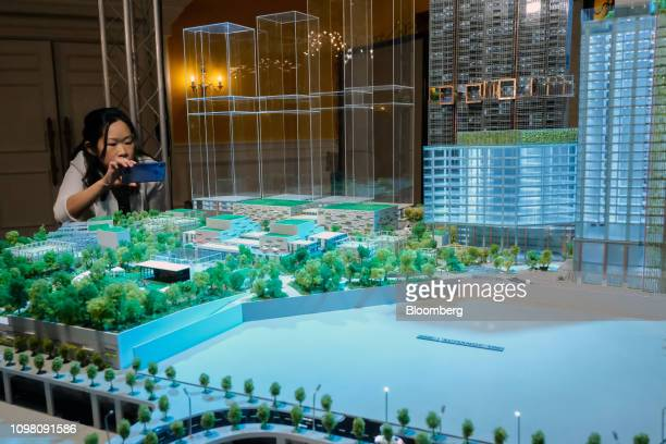 An attendee takes a photograph of a model during an event marking the launch of the Exchange TRX precinct in Kuala Lumpur Malaysia on Tuesday Feb 12...