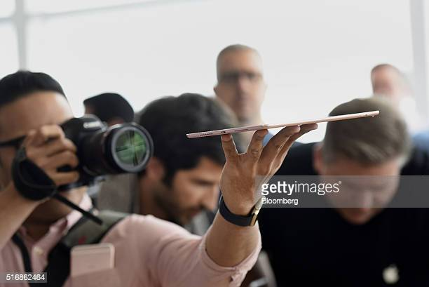 An attendee takes a photograph of a new Apple Inc 97 inch iPad Pro tablet computer after an event in Cupertino California US on Monday March 21 2016...