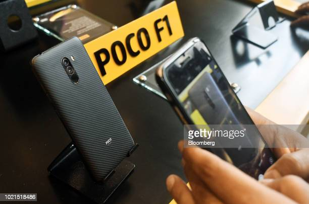 An attendee takes a photograph of a Xiaomi Corp Poco F1 smartphone on display during a product launch in New Delhi India on Wednesday Aug 22 2018...