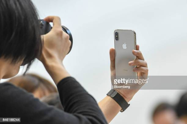 An attendee takes a photograph of an Apple Inc iPhone X during an event at the Steve Jobs Theater in Cupertino California US on Tuesday Sept 12 2017...