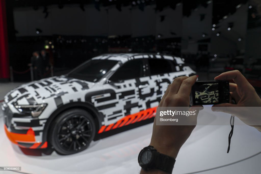 An attendee takes a photograph of an Audi AG e-tron prototype electric automobile on the opening day of the 88th Geneva International Motor Show in Geneva, Switzerland, on Tuesday, March 6, 2018. The show opens to the public on March 8, and will showcase the latest models from the world's top automakers. Photographer: Stefan Wermuth/Bloomberg via Getty Images