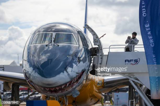 An attendee takes a photograph of an Embraer SA E190E2 passenger aircraft on day two of the Farnborough International Airshow 2018 in Farnborough UK...