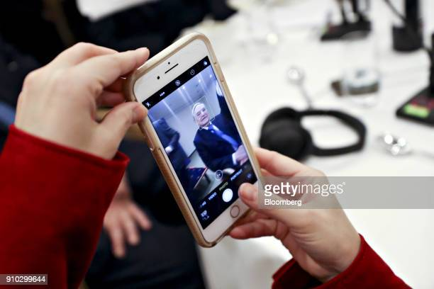 An attendee takes a photograph of George Soros billionaire and founder of Soros Fund Management LLC at an event on day three of the World Economic...