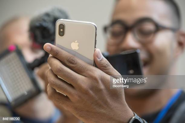An attendee takes a photograph of the Apple Inc iPhone X during an event at the Steve Jobs Theater in Cupertino California US on Tuesday Sept 12 2017...