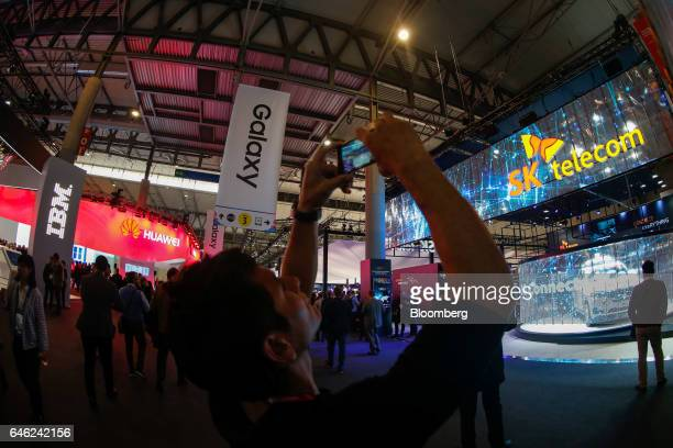 An attendee takes a photograph of the SK Telecom Co. Stand on the second day of Mobile World Congress in Barcelona, Spain, on Tuesday, Feb. 28, 2017....