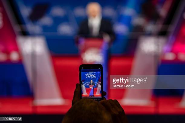 An attendee takes a photograph on their cellphone of Secretary of State Mike Pompeo speaking at the Conservative Political Action Conference 2020...