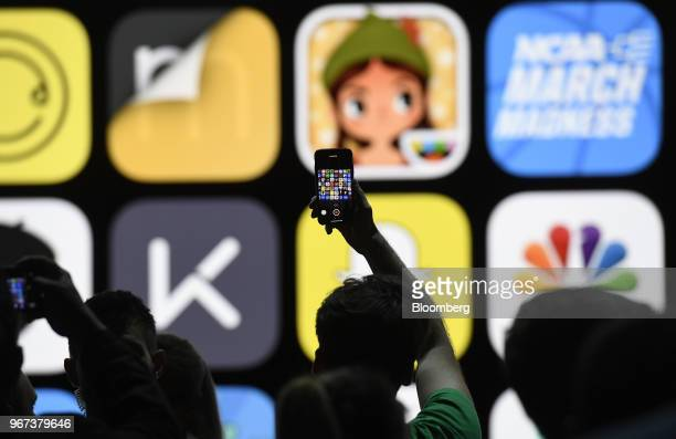 An attendee takes a photograph with an Apple Inc iPhone at the Apple Worldwide Developers Conference in San Jose California US on Monday June 4 2018...
