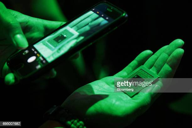 An attendee takes a picture while holding a processor for the Xbox One X console during the Microsoft Corp Xbox One X reveal event ahead of the E3...