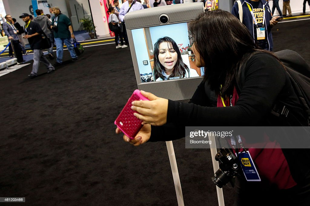 An attendee takes a 'selfie' photograph while having a video chat via Beam, a remote presence system manufactured by Suitable Technologies Inc., during the 2015 Consumer Electronics Show (CES) in Las Vegas, Nevada, U.S., on Thursday, Jan. 8, 2015. This year's CES will be packed with a wide array of gadgets such as drones, connected cars, a range of smart home technology designed to make everyday life more convenient and quantum dot televisions, which promise better color and lower electricity use in giant screens. Photographer: Patrick T. Fallon/Bloomberg via Getty Images
