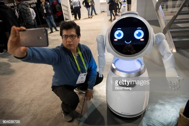 An attendee takes a selfie photograph with an Ubtech Robotics Inc Cruzr robot during the 2018 Consumer Electronics Show in Las Vegas Nevada US on...