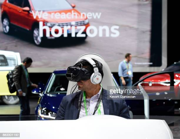 An attendee takes a virtual reality tour of a Volkswagon car during the auto trade show AutoMobility LA at the Los Angeles Convention Center November...