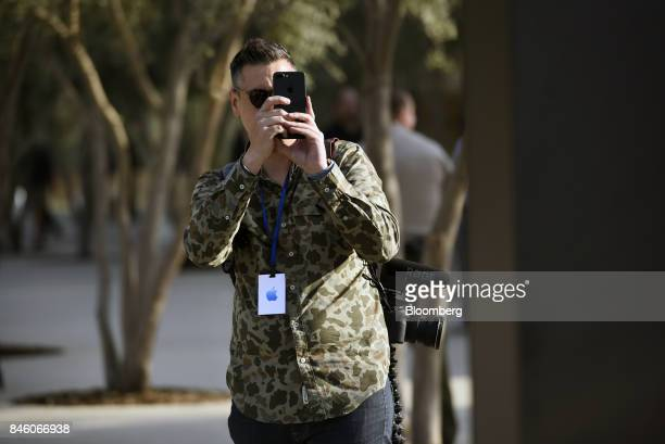 An attendee takes photograph with an Apple Inc iPhone ahead of an event at the Steve Jobs Theater in Cupertino California US on Tuesday Sept 12 2017...