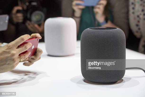 An attendee takes photographs of the Apple Inc HomePod speakers displayed during the Apple Worldwide Developers Conference in San Jose California US...