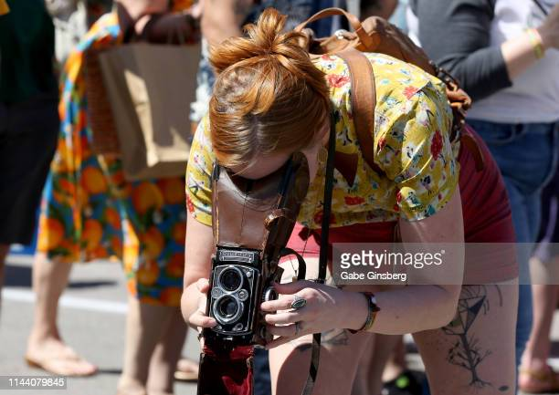 An attendee takes photos with a Rolleiflex camera during the Viva Las Vegas Rockabilly Weekend's car show at the Orleans Arena on April 20 2019 in...