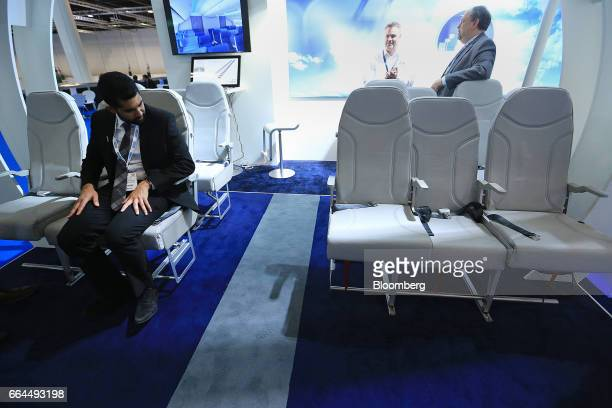An attendee tests a Molon Labe Designs side-slip passenger seat at the Aircraft Interiors Expo in Hamburg, Germany, on Tuesday, April 4, 2017....