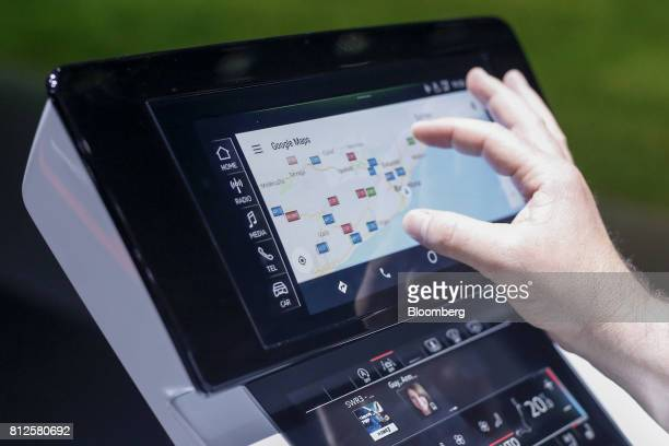 An attendee tests the Google Inc maps application on the touch screen inside an Audi AG A8 sedan automobile during a launch event in Barcelona Spain...