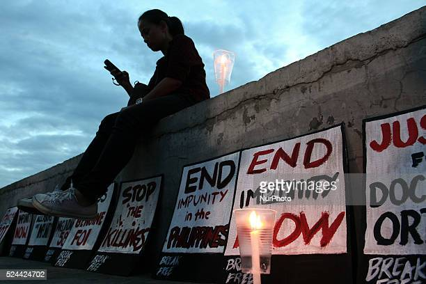 An attendee to the human chain event sits along Baywalk in Roxas Boulevard in Manila with the posters and candles lit in remembrance of the...