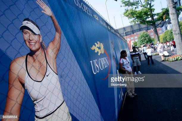 An attendee to the US Open poses in front of a promotional board with images of Maria Sharapova of Russia Roger Federer of Switzerland and other...