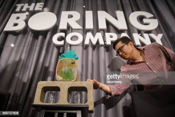 """An attendee touches a brick made from dirt removed by a tunnel boring machine featuring """"Gary,"""" a pet snail, perched atop it during a Boring Co...."""