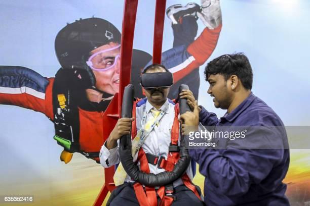 An attendee tries a free fall simulator at the Hindustan Aeronautics Ltd booth during the Aero India air show at Air Force Station Yelahanka in...