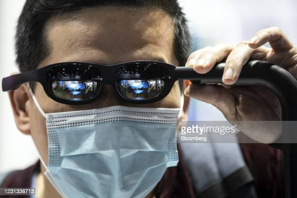 An attendee tries a pair of Nreal mixed-reality glasses at the MWC Shanghai exhibition in Shanghai, China, on Tuesday, Feb. 23, 2021. The Shanghai...