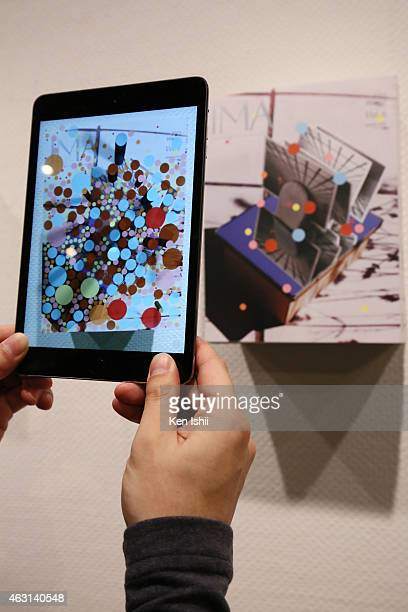 An attendee tries 'IMA ARART Exhibition' by amana and Matilde with his ipad at the Media Ambition Tokyo 2015 at IMA Gallery on February 10 2015 in...