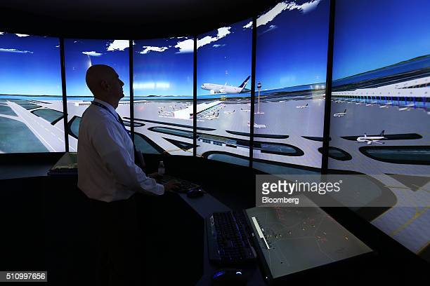 An attendee tries out a Changi Airport control tower simulator developed by Mitre Corp at the Singapore Airshow held at the Changi Exhibition Centre...