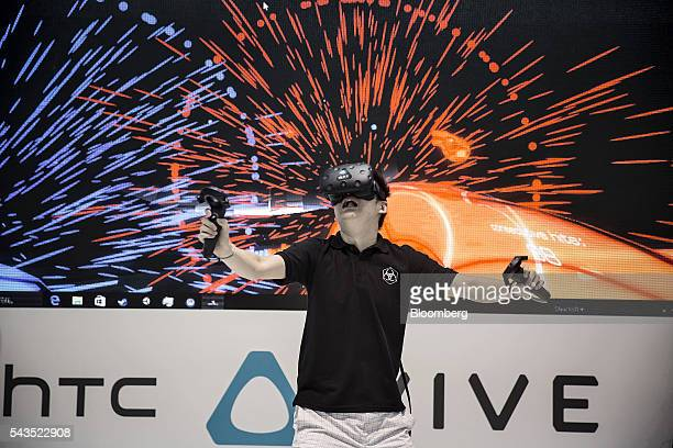 An attendee tries out a virtual reality game on HTC Corp's Vive headset at the Mobile World Congress Shanghai in Shanghai China on Wednesday June 29...