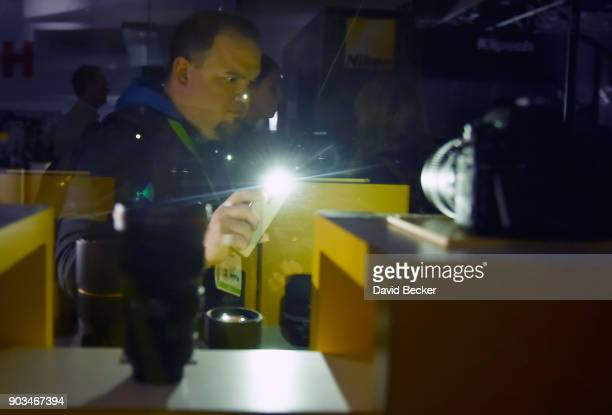 An attendee uses a flashlight on his smartphone to view a display at the Nikon booth after power was lost inside the central hall during CES 2018 at...