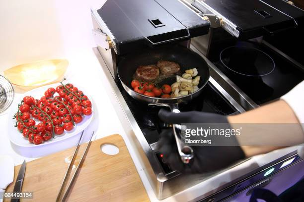 An attendee uses a frying pan during a demonstration to show the operation of a flight safe cooking system by Lufthansa Technik AG at the Aircraft...