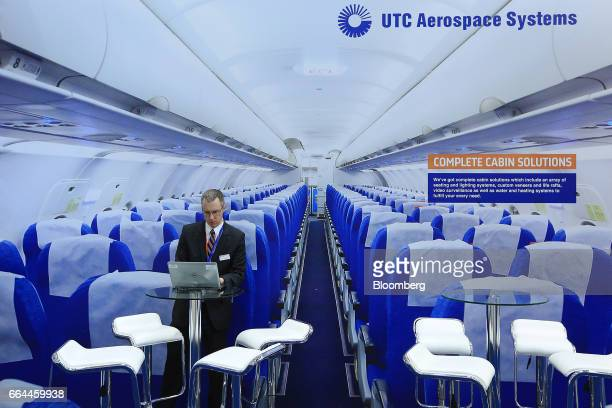 An attendee uses a laptop computer in front of a large photograph of a passenger aircraft interior in the UTC Aerospace Systems pavilion at the 2017...