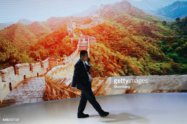 An attendee uses a mobile device as he passes a large digital display screen showing a picture of a section of the Great Wall of China on the second...