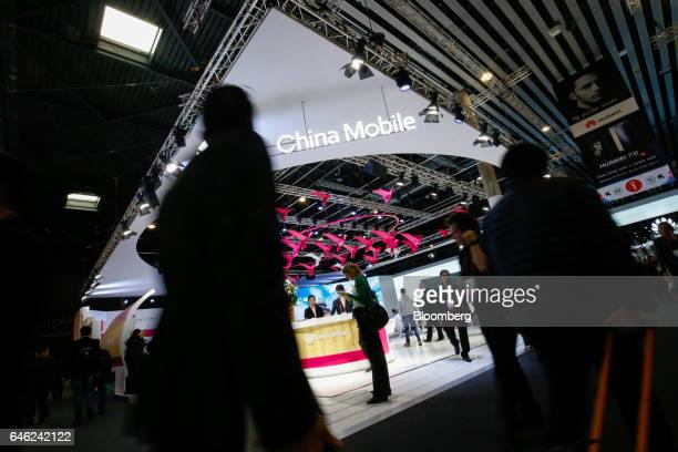 An attendee uses a mobile device as she passes the China Mobile stand on the second day of Mobile World Congress in Barcelona, Spain, on Tuesday,...