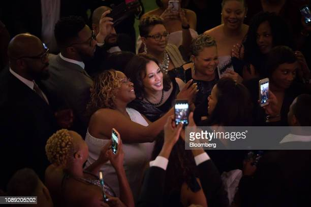 An attendee uses a mobile device to take a selfie photograph with Senator Kamala Harris a Democrat from California during the Alpha Kappa Alpha...