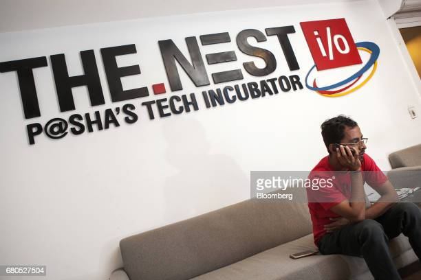 An attendee uses a mobile phone beneath signage for The Nest i/o tech incubation center in Karachi Pakistan on Monday April 24 2017 Jehan Ara founder...