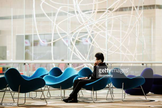 An attendee uses a mobile phone in front of the 'Petalclouds' kinetic installation during a media preview of the new Terminal 4 at Changi Airport in...