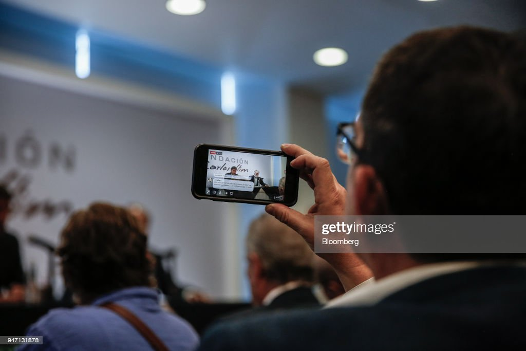 An attendee uses a mobile phone to record a Facebook Inc. Live stream of Carlos Slim, chairman emeritus of America Movil SAB, speaking during a press conference in Mexico City, Mexico, on Monday, April 16, 2018. Slim said that Mexico has plenty of advantages in the NAFTA negotiations. Photographer: Alejandro Cegarra/Bloomberg via Getty Images