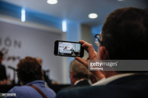 An attendee uses a mobile phone to record a Facebook Inc Live stream of Carlos Slim chairman emeritus of America Movil SAB speaking during a press...