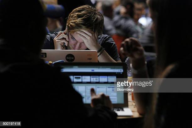 An attendee uses a mobile phone whilst looking at his laptop computer screen in the TechCrunch Disrupt London 2015 Hackathon in London UK on Saturday...