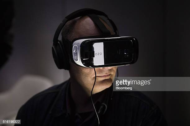 An attendee uses a Samsung Gear VR virtual reality headset to view the Ozo a virtual reality camera manufactured by Nokia Oyj at the European launch...