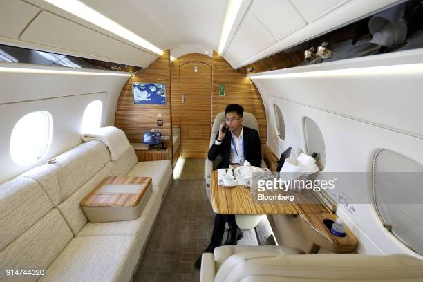 An attendee uses a smartphone inside an Embraer SA Legacy 500 jet during the Singapore Airshow held at the Changi Exhibition Centre in Singapore on...
