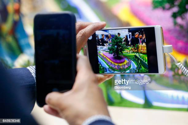 An attendee uses a smartphone to take a photograph of a Axon 7 smartphone manufactured by ZTE Corp on the opening day of the Mobile World Congress in...