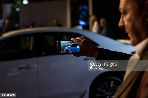 An attendee uses a smartphone to take a photograph of the new2018 Toyota Motor Corp. Corolla vehicle during the company's launch event in Sao Paulo,...