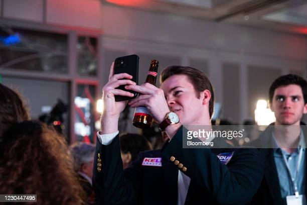 An attendee uses a smartphone to take photographs as results come in during a GOP election night party in Atlanta, Georgia, U.S., on Tuesday, Jan. 5,...