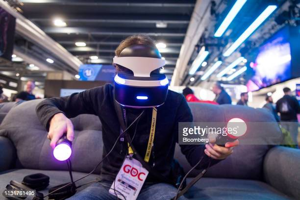An attendee uses a Sony Corp. PlayStation virtual reality headset and controllers at the Game Developers Conference in San Francisco, California,...