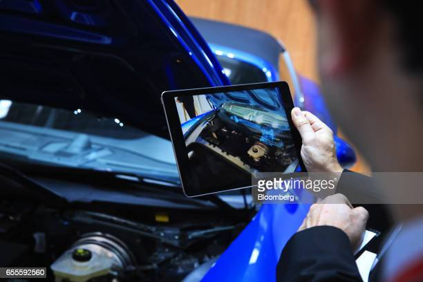 An attendee uses a tablet device loaded with augmented reality vision tracking software by VisionLib to view the internal workings of the engine of a...