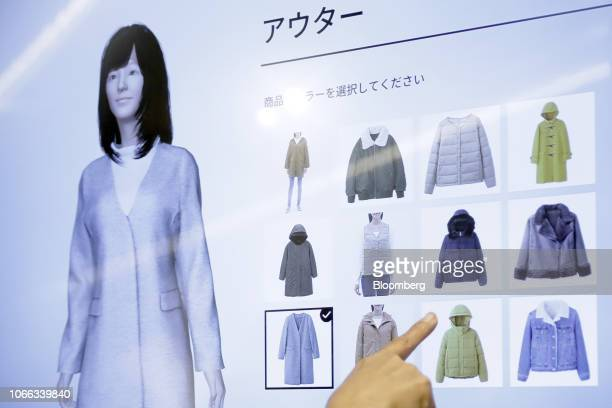 An attendee uses a touch screen display to try on clothes on a virtual avatar during a media event at the GU Style Studio store operated by Fast...