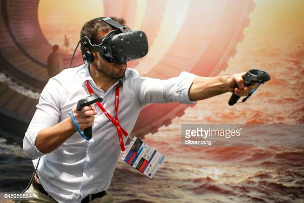 An attendee uses a Vive virtual reality headset, manufactured by HTC Corp., in a boxing match simulation on the opening day of the Mobile World...