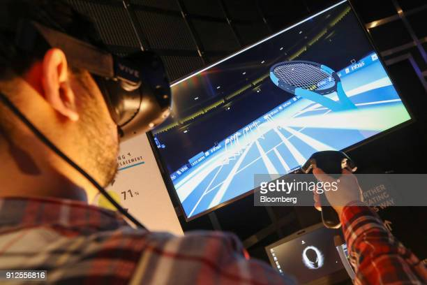 An attendee uses a Vive virtual reality headset manufactured by HTC Corp while playing a computer simulated tennis match on the Infosys Ltd stand...